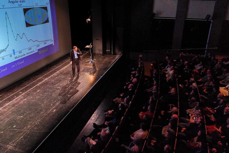 """Fotografie: Sprecher Prof. Dr. Christof Wetterich erklärt dem Publikum eine Grafik bei """"Physik im Theater"""" in Mainz"""