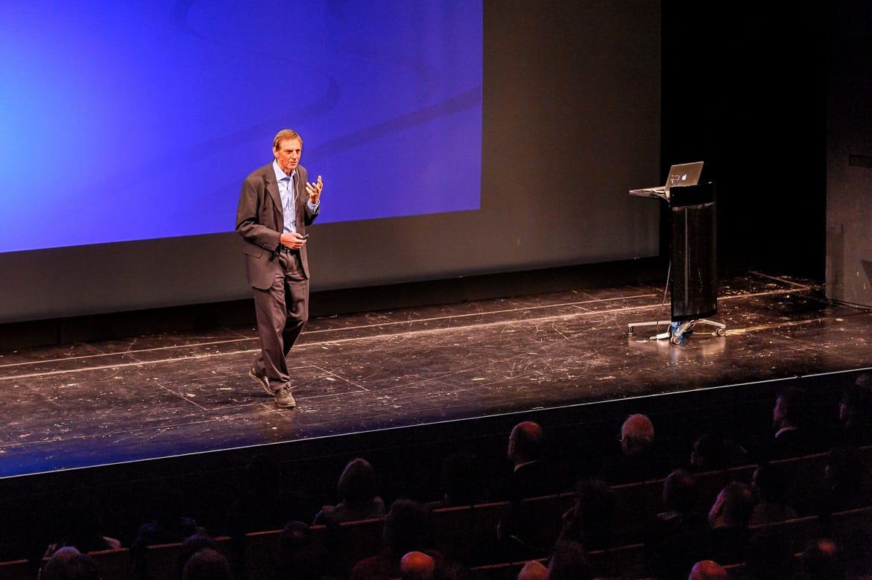 """Fotografie: Sprecher Prof. Dr. Christof Wetterich erklärt während des Vortrages bei """"Physik im Theater"""" in Mainz"""