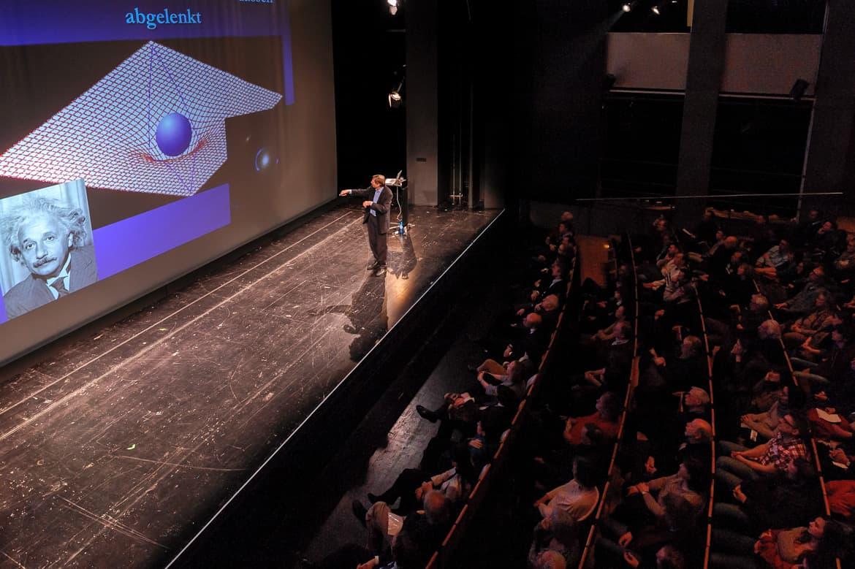 """Fotografie: Sprecher Prof. Dr. Christof Wetterich von schräg oben fotografiert während des Vortrages bei """"Physik im Theater"""" in Mainz"""