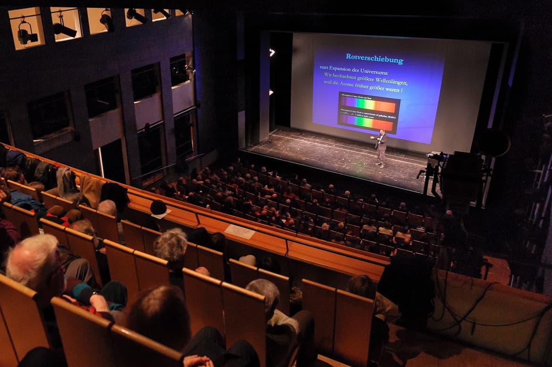 """Fotografie: Sprecher Prof. Dr. Christof Wetterich von der letzten Reihe des Saals fotografiert während des Vortrages bei """"Physik im Theater"""" in Mainz"""